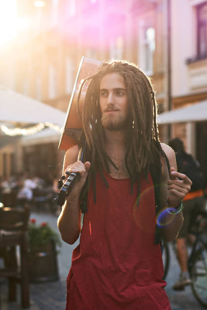 Young handsome bearded man hippie with dreadlocks snapping fingers on an old city street full of sunlight with a guitar Young handsome bearded man hippie in the summer city rastafarian stock pictures, royalty-free photos & images
