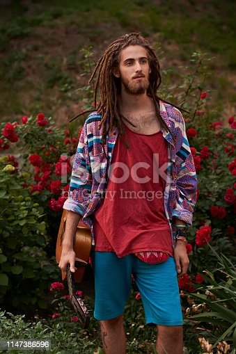 Young handsome bearded man hippie in the summer city