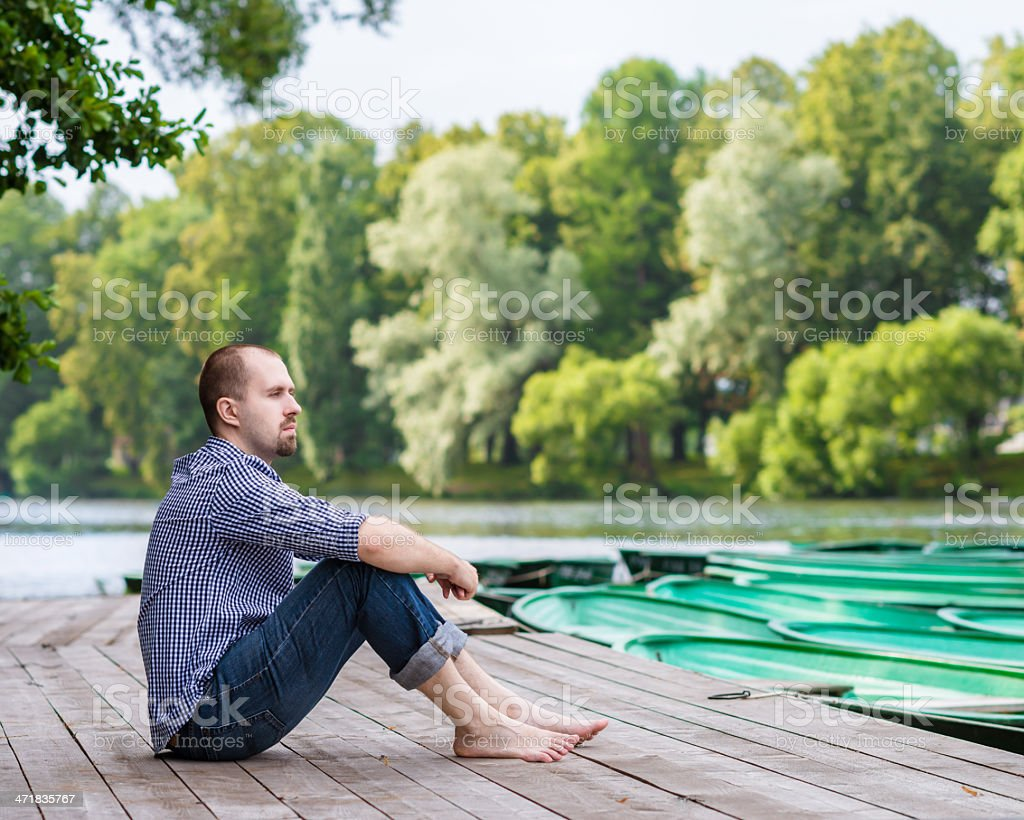 Young handsome bearded man sitting on wooden pier royalty-free stock photo