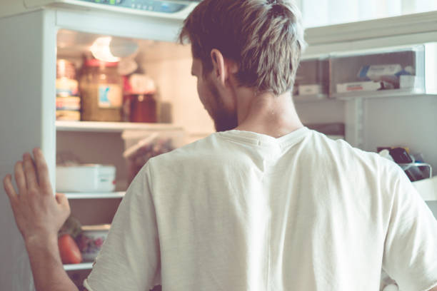 young handsome bearded man standing near opended fridge at home kitchen - frigorifero foto e immagini stock
