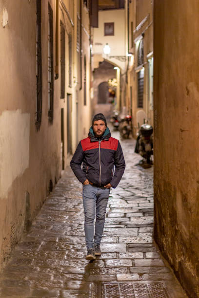 A young handsome bearded man walking by the streets of Florence at night while looking at the camera stock photo