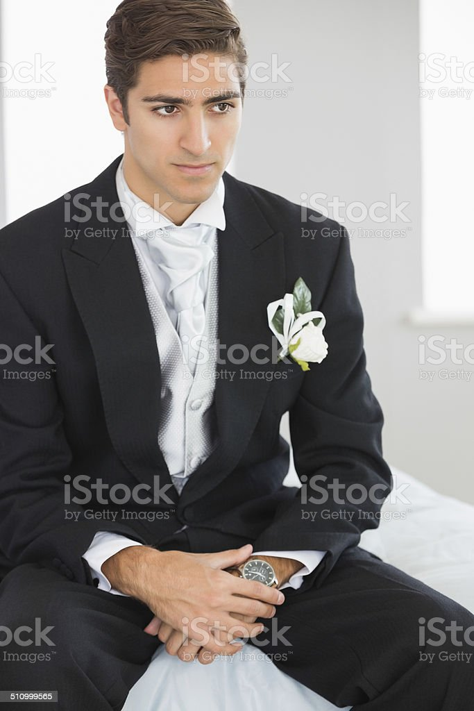 Young handsome bridegroom sitting on bed stock photo