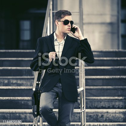 907934274 istock photo Young handsome business man calling on cell phone on city street 1144870150