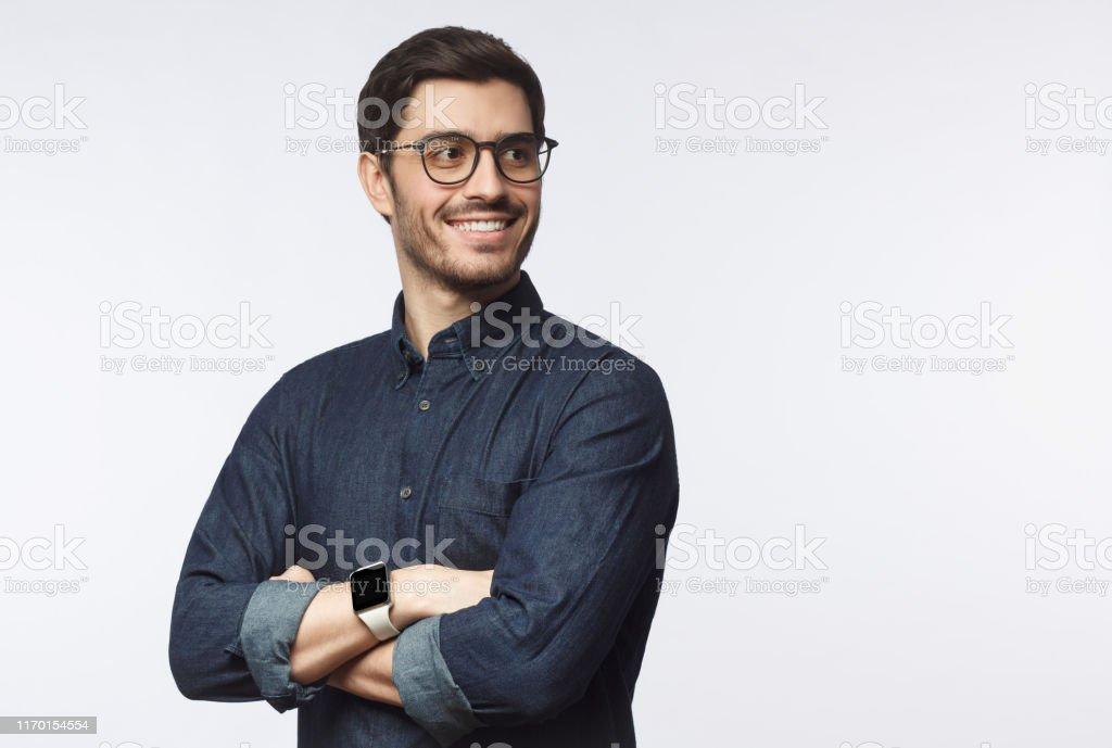 Genç yakışıklı iş adamı bilek akıllı saat ile rahat kot gömlek giymiş, gri arka plan üzerinde izole - Royalty-free 20'lerinde Stok görsel