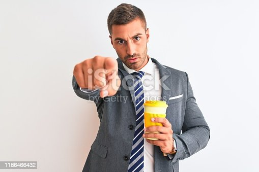 Young handsome business man drinking take away coffee over isolated background pointing with finger to the camera and to you, hand sign, positive and confident gesture from the front