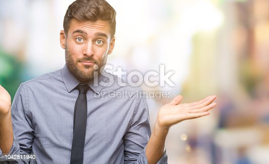 Young handsome business man over isolated background clueless and confused expression with arms and hands raised. Doubt concept.