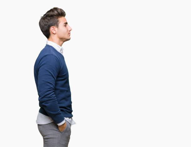 年輕英俊的商人在孤立的背景下尋找的一面, 放鬆的輪廓姿勢與自然的臉與自信的微笑。 - 側視 個照片及圖片檔
