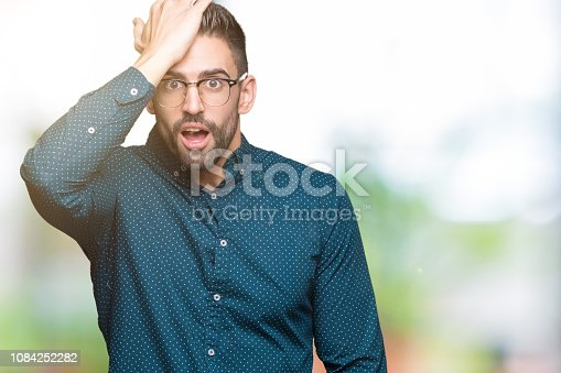 1046559700istockphoto Young handsome business man wearing glasses over isolated background surprised with hand on head for mistake, remember error. Forgot, bad memory concept. 1084252282
