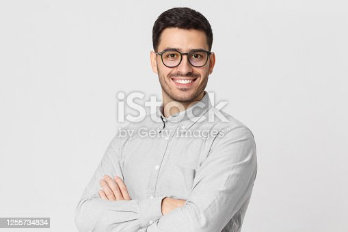 Young handsome business man wearing gray shirt and eyeglasses, holding arms crossed, smiling and feeling confident, isolated