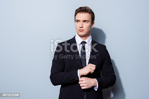 973213156 istock photo Young handsome businessman banker in a suit is fixing his cuff links, he stands on pure light background. So mature and virile, hot and confident 937323266