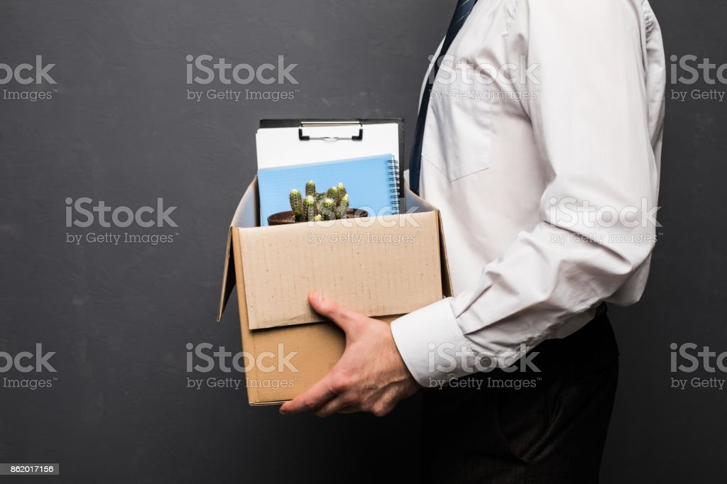 Young handsome businessman in light modern office with carton box. Last day at work. Upset office worker is fired. stock photo