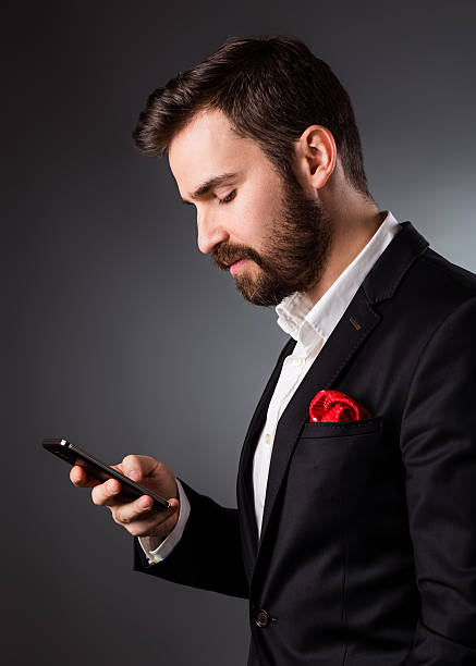 Young handsome businessman in suit holding a phone stock photo