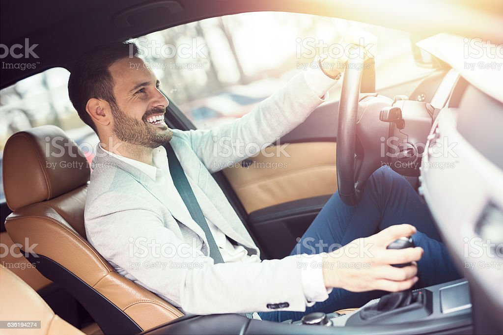 Young handsome businessman is driving a car stock photo