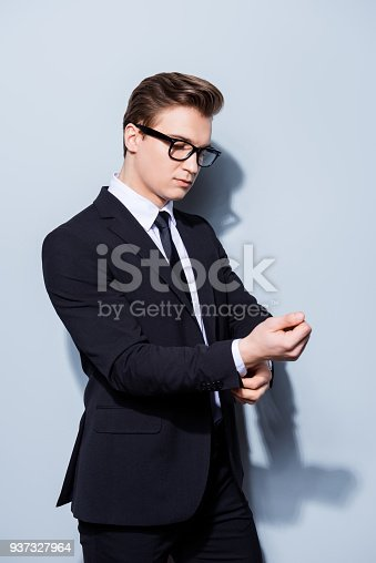 973213156 istock photo Young handsome businessman lawyer in a suit is fixing his cuffl inks, he stands on pure light background. So mature and virile, hot and confident 937327964