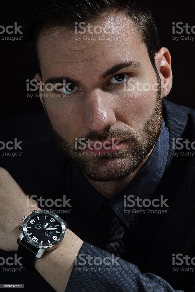 Young handsome businessman on dark background stock photo