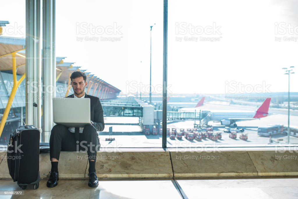 young handsome businessman using his laptop and mobile phone at the airport waiting for his flight and smiling stock photo