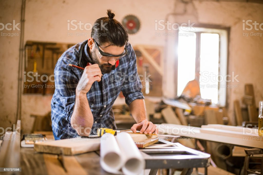 Young handsome carpenter drawing sketches stock photo
