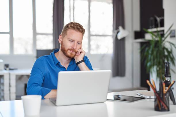 Junge hübsche kaukasisch bärtige Mitarbeiter auf Schreibtisch und mit Laptop lehnen, während im modernen Büro sitzen. Start-up-Geschäftskonzept. – Foto