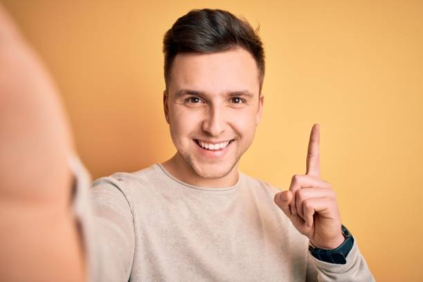 Young handsome caucasian man talking a selfie picture over yellow isolated background surprised with an idea or question pointing finger with happy face, number one stock photo