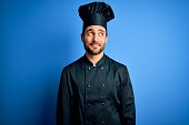 istock Young handsome chef man with beard wearing cooker uniform and hat over blue background smiling looking to the side and staring away thinking. 1212961223