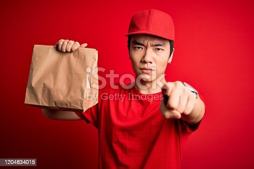 Young handsome chinese delivery man holding takeaway paper bag with food pointing with finger to the camera and to you, hand sign, positive and confident gesture from the front