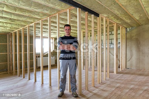 istock Young handsome constructor man standing in the middle of big spacious light empty attic room with oak floor, insulated ceiling and wooden frame for future walls. Construction and renovation concept. 1155293518