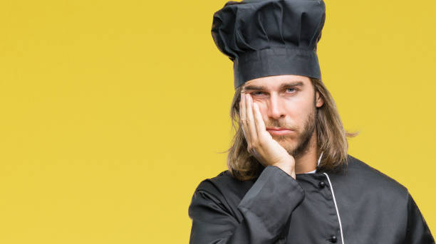 young handsome cook man with long hair over isolated background thinking looking tired and bored with depression problems with crossed arms. - chef triste foto e immagini stock