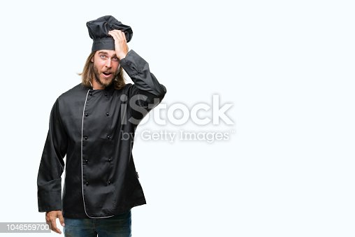 1046559700istockphoto Young handsome cook man with long hair over isolated background surprised with hand on head for mistake, remember error. Forgot, bad memory concept. 1046559700