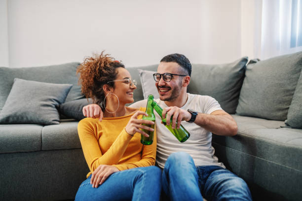 Young handsome couple relaxing at home. They are toasting with beer. Sunday afternoon. stock photo