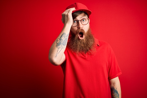 1046559700 istock photo Young handsome delivery man wearing glasses and red cap over isolated background surprised with hand on head for mistake, remember error. Forgot, bad memory concept. 1205015884