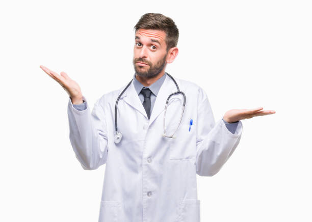 Young handsome doctor man over isolated background clueless and confused expression with arms and hands raised. Doubt concept. Young handsome doctor man over isolated background clueless and confused expression with arms and hands raised. Doubt concept. shrugging stock pictures, royalty-free photos & images