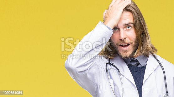 1046559700istockphoto Young handsome doctor man with long hair over isolated background surprised with hand on head for mistake, remember error. Forgot, bad memory concept. 1050881084