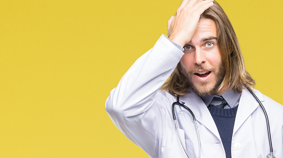 1046559700 istock photo Young handsome doctor man with long hair over isolated background surprised with hand on head for mistake, remember error. Forgot, bad memory concept. 1050881084