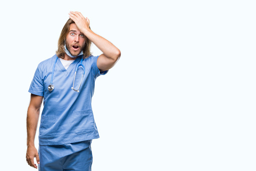 1046559700 istock photo Young handsome doctor man with long hair over isolated background surprised with hand on head for mistake, remember error. Forgot, bad memory concept. 1081495010