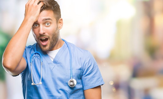 1046559700 istock photo Young handsome doctor surgeon man over isolated background surprised with hand on head for mistake, remember error. Forgot, bad memory concept. 1081512858