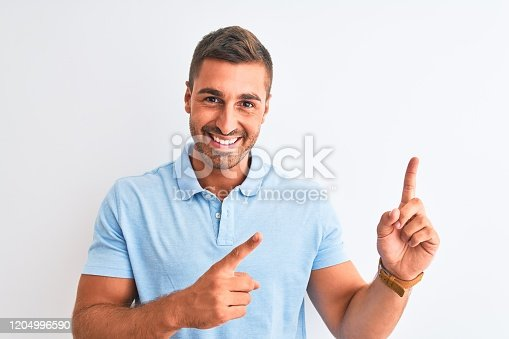 1045886560 istock photo Young handsome elegant man wearing blue t-shirt over isolated background smiling and looking at the camera pointing with two hands and fingers to the side. 1204996590