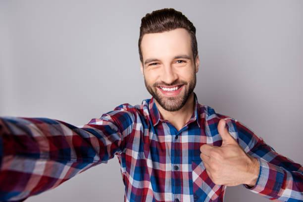 junge hübsche aufgeregt kerl in freizeitkleidung daumen auftauchen und nehmen eine selfie vor grauem hintergrund - happy weekend bilder stock-fotos und bilder