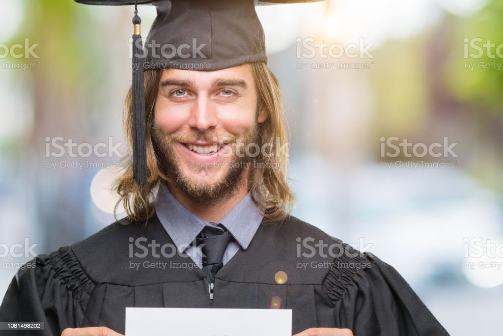 Young handsome graduate man with long hair holding blank paper over isolated background with a happy face standing and smiling with a confident smile showing teeth stock photo