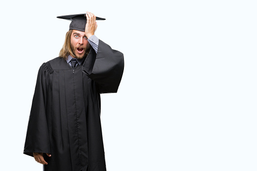 1046559700 istock photo Young handsome graduated man with long hair over isolated background surprised with hand on head for mistake, remember error. Forgot, bad memory concept. 1081495178