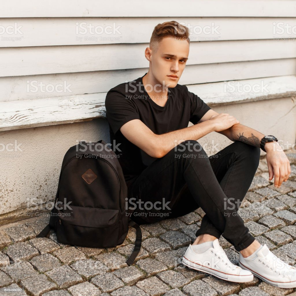 Young handsome guy in a trendy black dress and white shoes sitting near wooden wall. Black backpack. stock photo