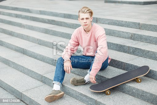 846124694 istock photo young handsome guy in a trendy pink sweater with a skateboard sits on the steps 846124536
