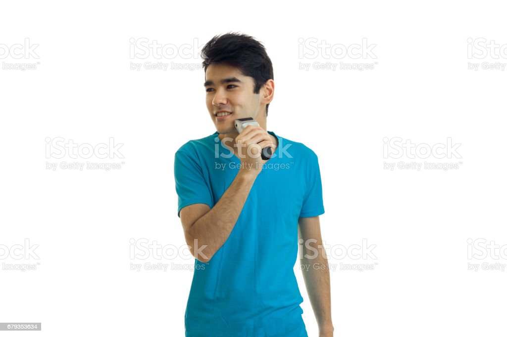 young handsome guy in a t-shirt looking sideways and shaves shaving machine face royalty-free stock photo
