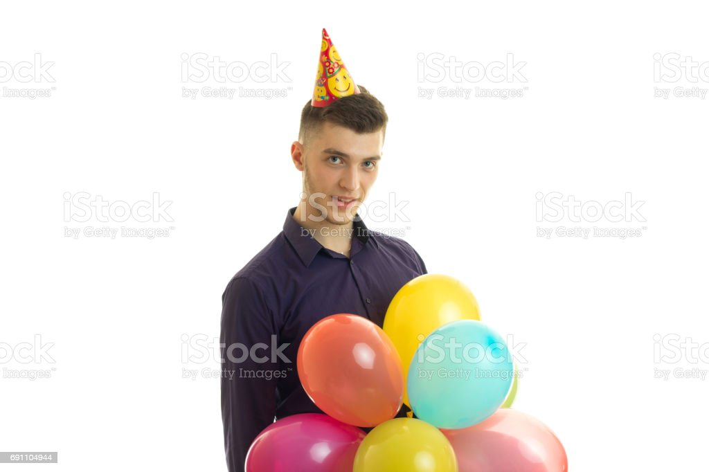 young handsome guy looks into the camera and holds balls stock photo