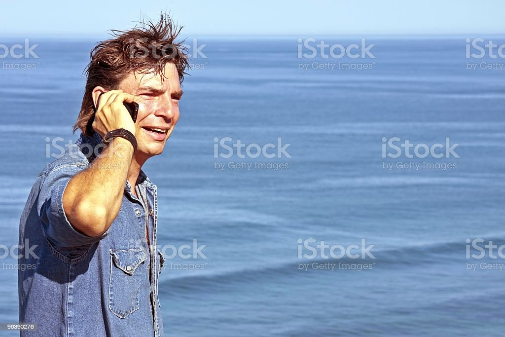 Young handsome guy making a phone call at the ocean - Royalty-free Adult Stock Photo