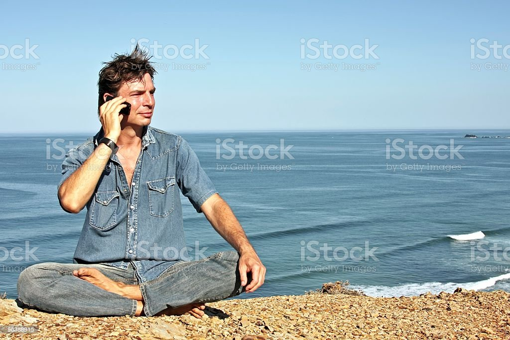 Young handsome guy making a phonecall on the rocks - Royalty-free Adult Stock Photo