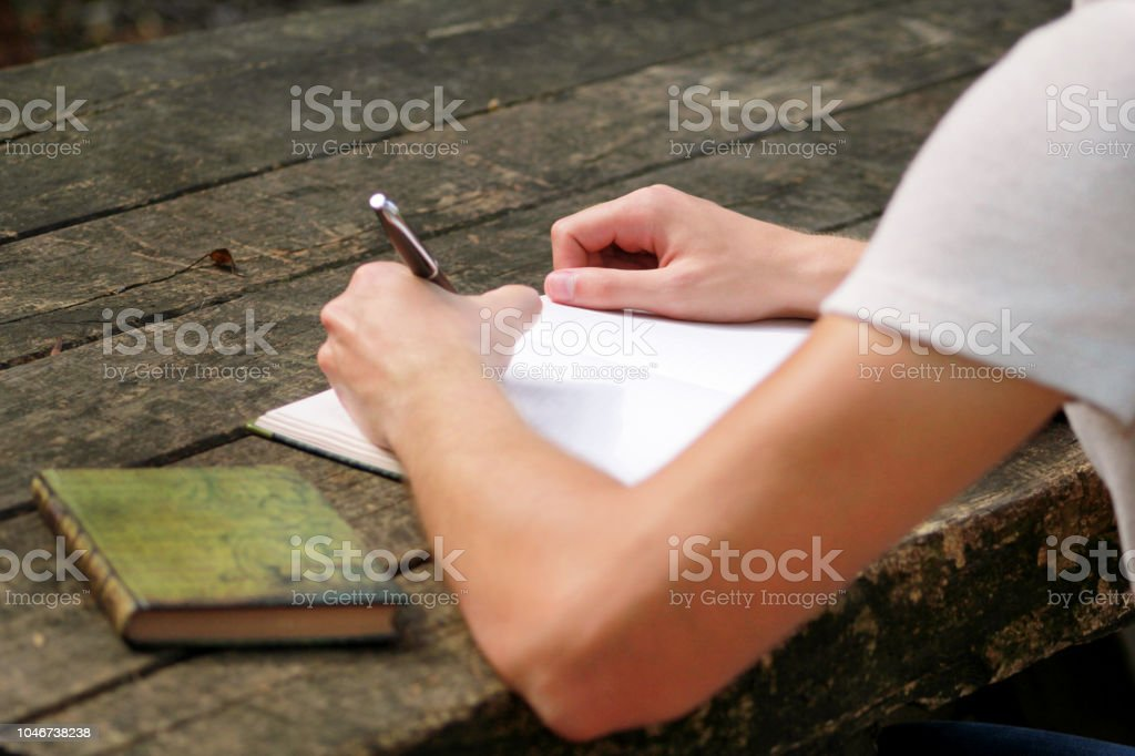 Young handsome guy sitting at wooden table, writing a book, doing homework, taking notes, learning, contemplating and writing down his thoughts and lessons while enjoying the outdoors in forest. stock photo