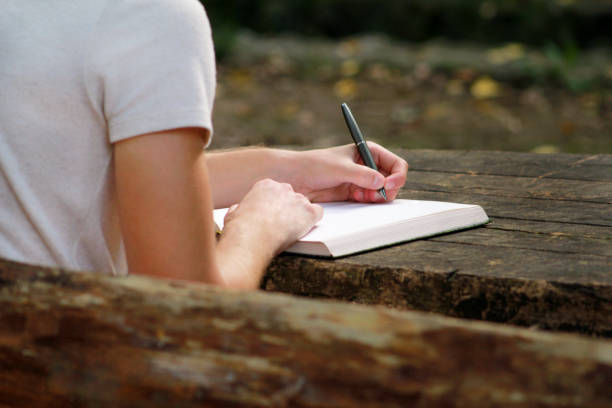 Bonito rapaz sentado na mesa de madeira, escrevendo um livro, fazendo a lição de casa, tomando notas, aprendizagem, contemplando e escrevendo seus pensamentos e lições enquanto desfruta da vida ao ar livre na floresta. - foto de acervo