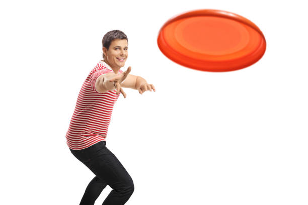 Young handsome guy throwing a frisbee Young handsome guy throwing a frisbee isolated on white background plastic disc stock pictures, royalty-free photos & images