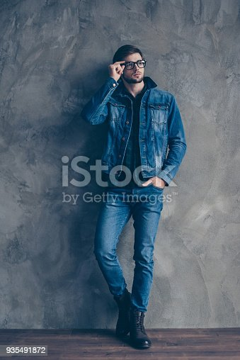 611630440 istock photo young handsome guy with glasses and a denim suit stands on a gray background and looks to the side 935491872