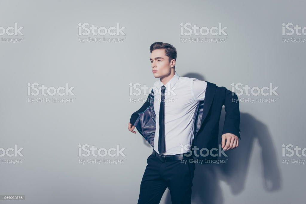 72ac08aab0228 Chico joven guapo con peinado perfecto en juego con su chaqueta contra el  fondo gris foto